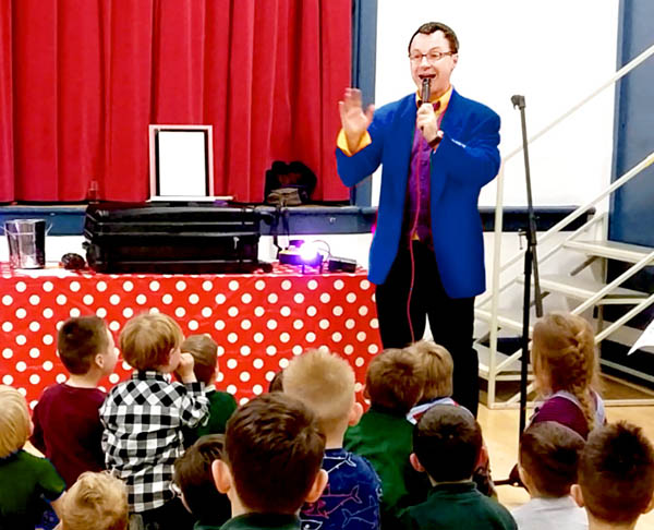 A magician entertains in a school hall, speaking on a microphone in front of an audience of children