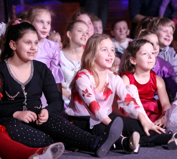 A child audience watches a visiting educational show in a school