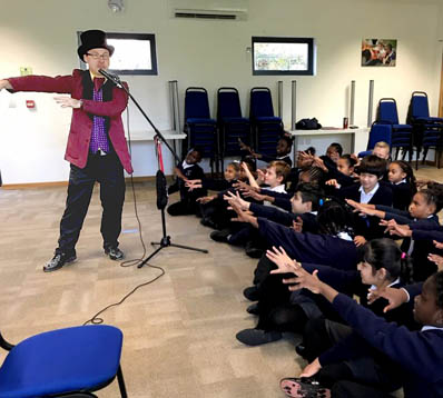 A school magician performs a magical gesture, copied by an audience of children