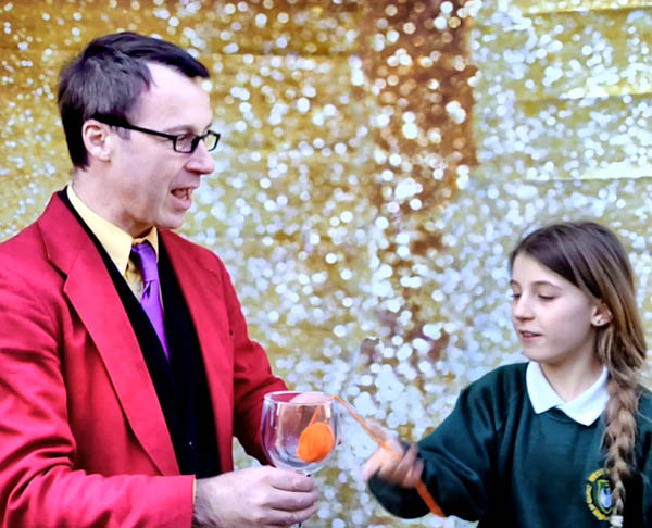 A magician, performing at a school, has a girl helper pull on a length of orange wool